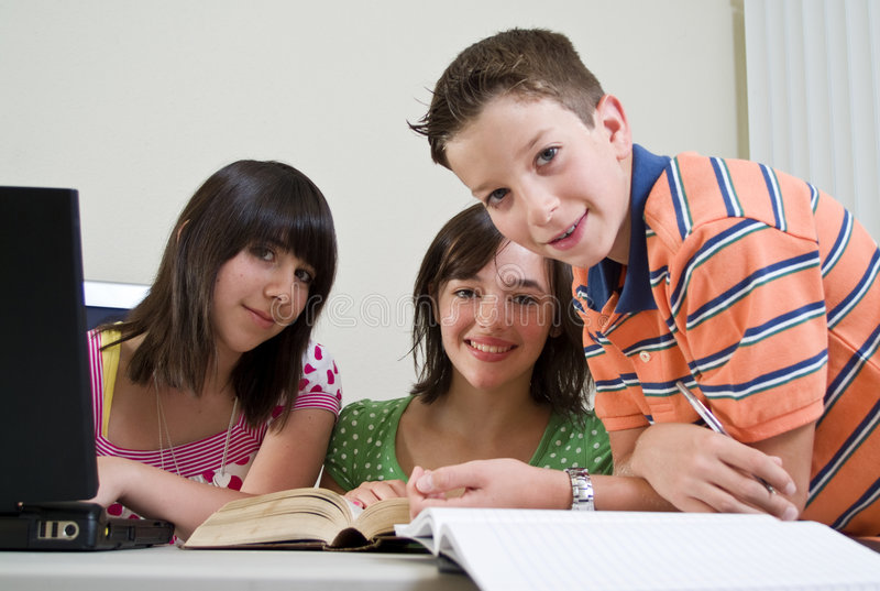 Homework Time. Three kids studying together with focus on girl in foreground stock images