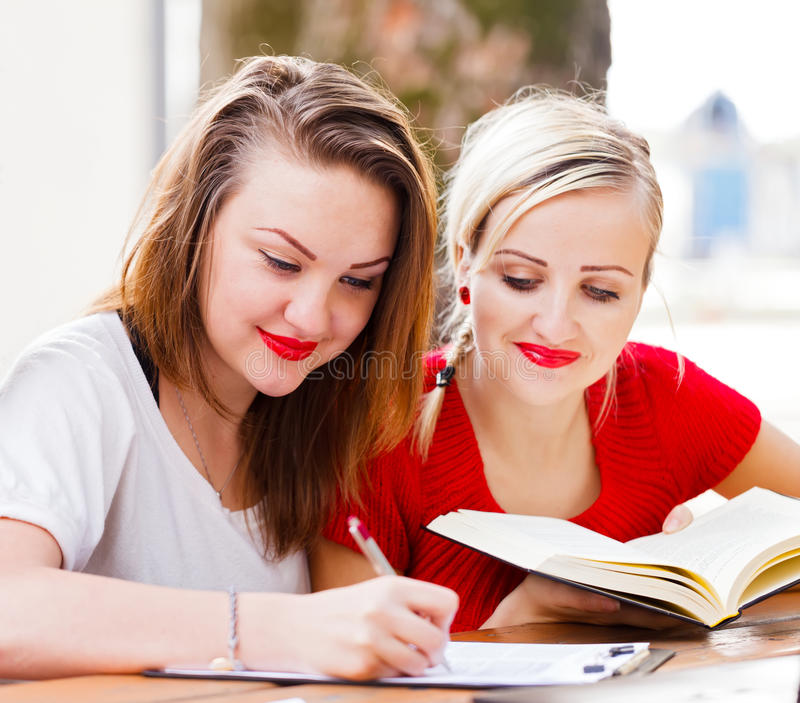 Homework together. Beautiful student girls in the university campus studying for exams, doing homework royalty free stock photos