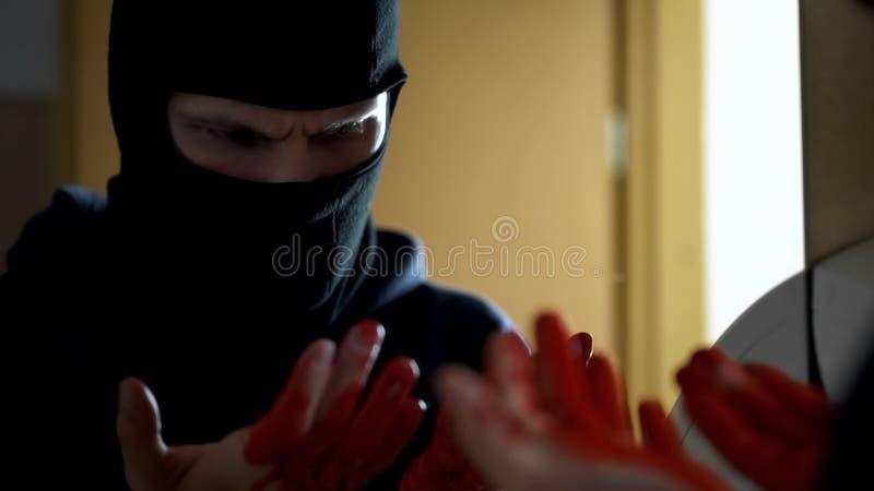 Homicidio, ladrón profesional que mira las manos sangrientas delante del espejo fotos de archivo libres de regalías