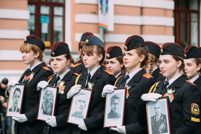 Homiel', Bielorussia Formazione in marcia di ragazze del cadetto dalla scuola del cadetto dello stato di Homiel'con i ritratti fotografie stock libere da diritti