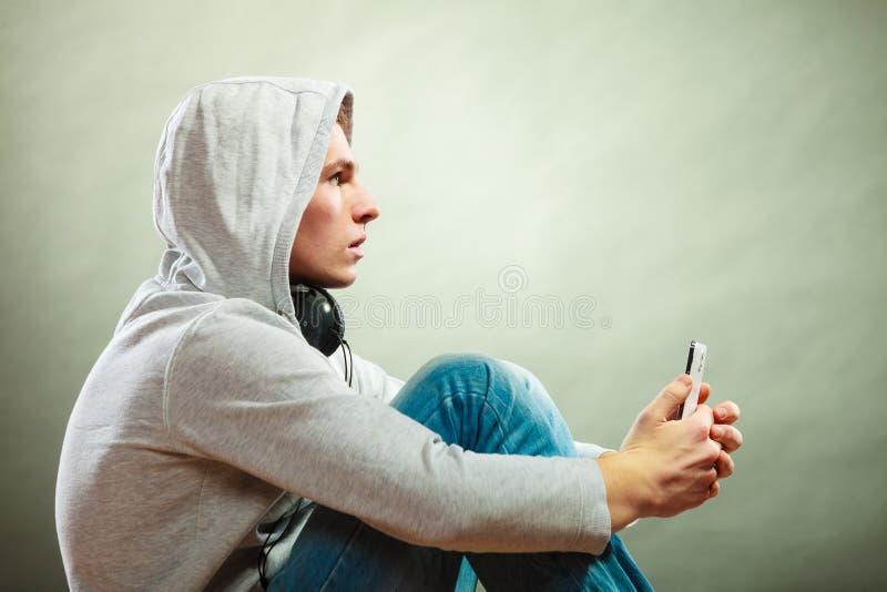 Homme à capuchon avec la musique de écoute d'écouteurs photos stock