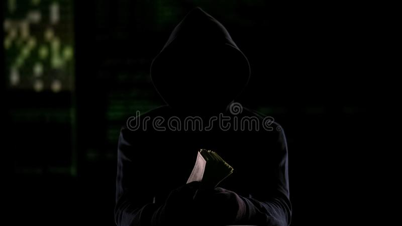 Homme à capuchon dans l'obscurité tenant l'argent liquide, la récompense de meurtre commandité ou l'argent volé photo libre de droits