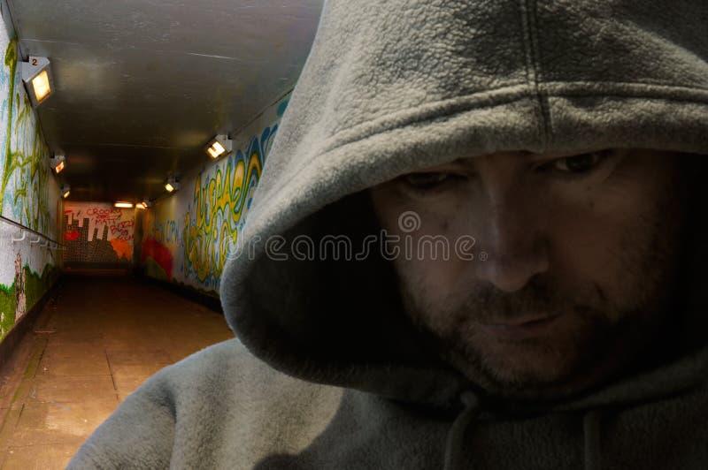 Homme à capuchon dans le souterrain graffiti-décoré photographie stock