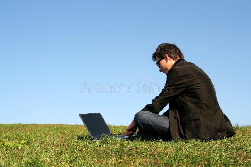 Homme à l'aide d'un ordinateur portatif à l'extérieur images libres de droits