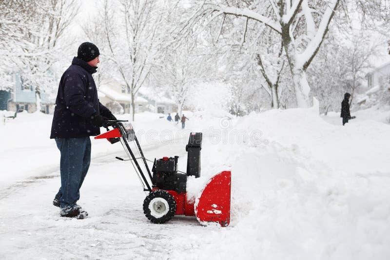 Homme à l'aide d'une souffleuse de neige photo stock