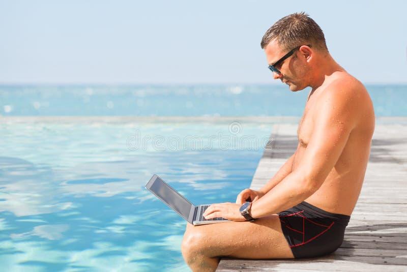 Homme à l'aide de l'ordinateur par la piscine images libres de droits