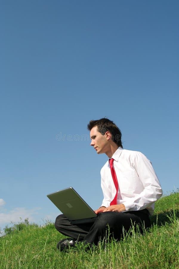 Homme à l'aide de l'ordinateur portatif à l'extérieur photos stock