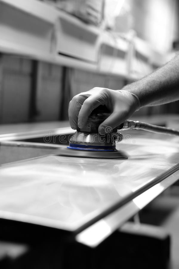 Homme à l'aide de la ponceuse orbitale pour préparer un panneau en métal avec la couleur sélective photo libre de droits