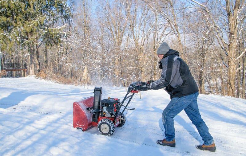 Homme à l'aide de la souffleuse de neige image libre de droits