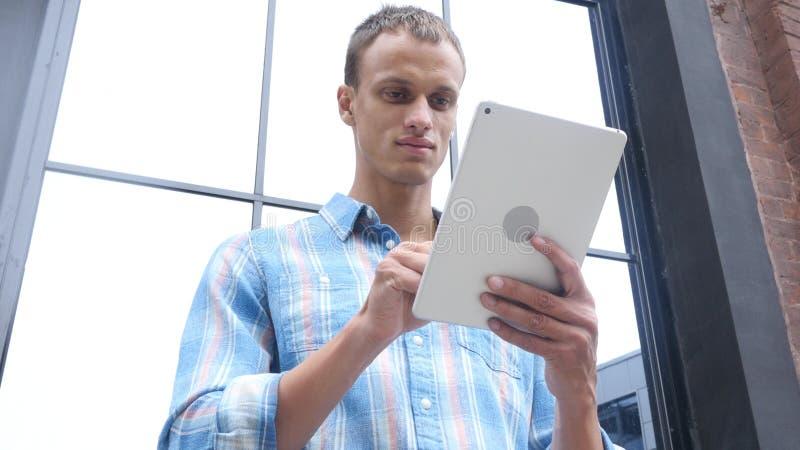 Homme à l'aide de la tablette tenant le bureau proche photographie stock