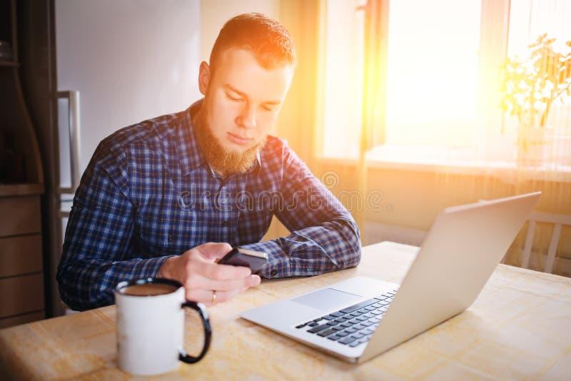 Homme à l'aide de l'ordinateur portable et du téléphone intelligent à la table dans le bureau contre la fenêtre photo libre de droits