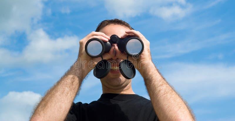 Homme à l'aide des jumelles à l'extérieur photographie stock libre de droits