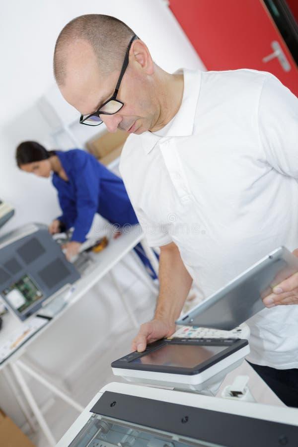 Homme à l'aide du comprimé pour découvrir le problème d'imprimante photos stock