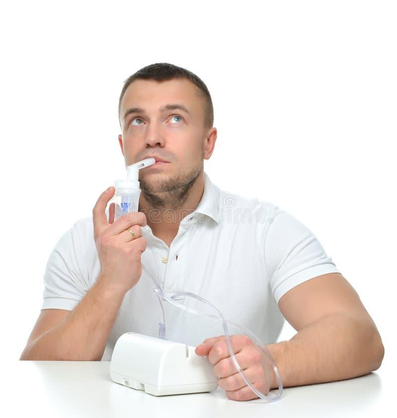 Homme à l'aide du nébuliseur pour le traitement respiratoire d'asthme d'inhalateur photos stock
