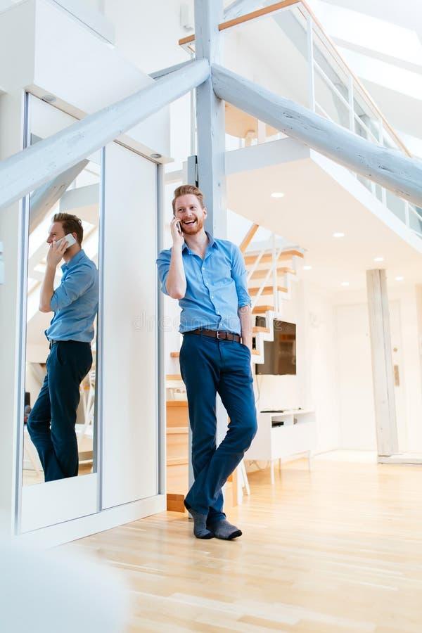 Homme à l'aide du téléphone en bel appartement moderne photos libres de droits