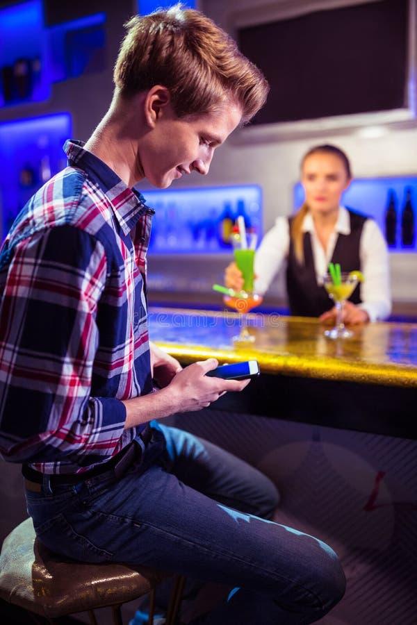Homme à l'aide du téléphone portable avec la position de barman photographie stock