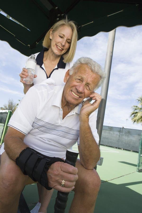Homme à l'aide du téléphone portable sur le court de tennis image libre de droits