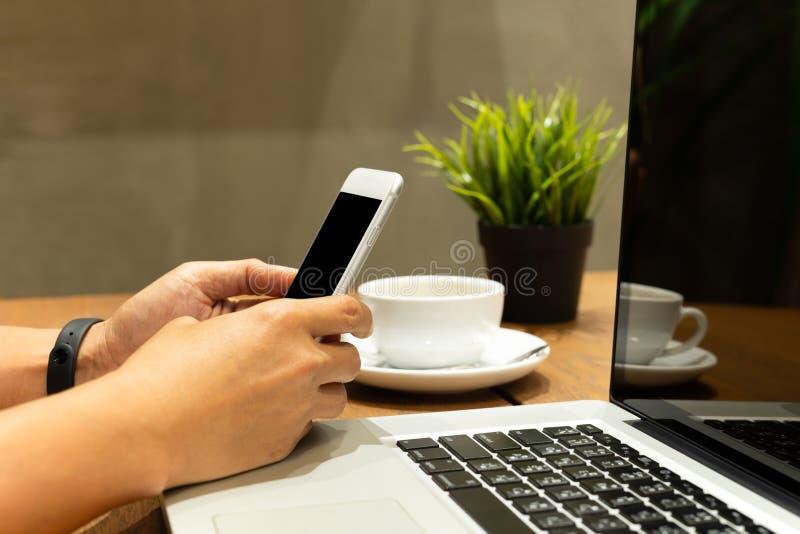 Homme à l'aide du téléphone portable tout en travaillant sur l'ordinateur portable au café image stock