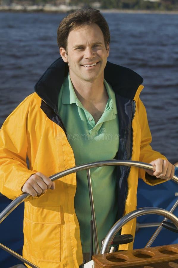 Homme à la barre du bateau à voiles photos libres de droits