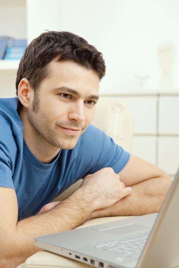 homme à la maison d'ordinateur portatif utilisant des jeunes images libres de droits