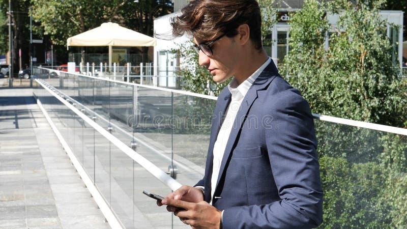 Homme à la mode bel à l'aide du téléphone portable pour dactylographier le texte image libre de droits