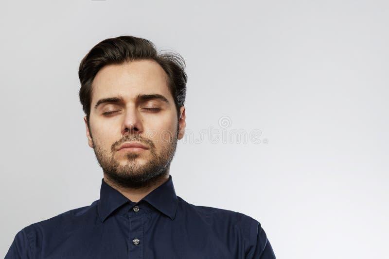 Homme à la mode hispanique bel posant avec les yeux fermés d'isolement sur un fond vide blanc images stock