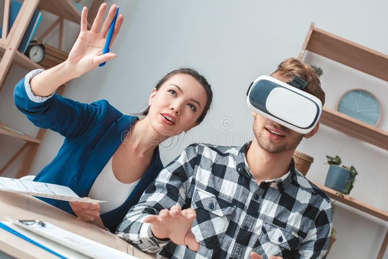 Homme à la vraie agence immobilière s'asseyant dans l'agent de casque de réalité virtuelle favorisant le service de client images stock