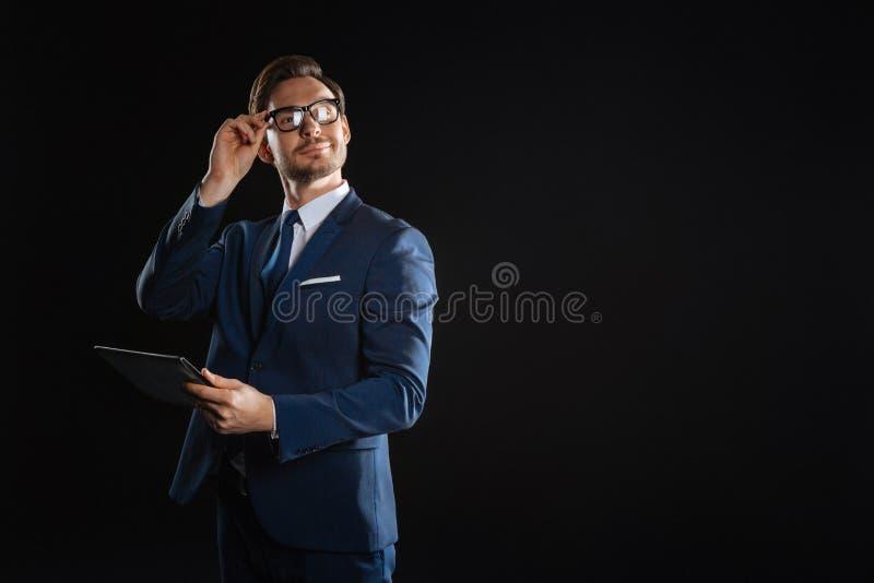 Homme à lunettes réussi tenant le comprimé touchant à ses verres photographie stock libre de droits