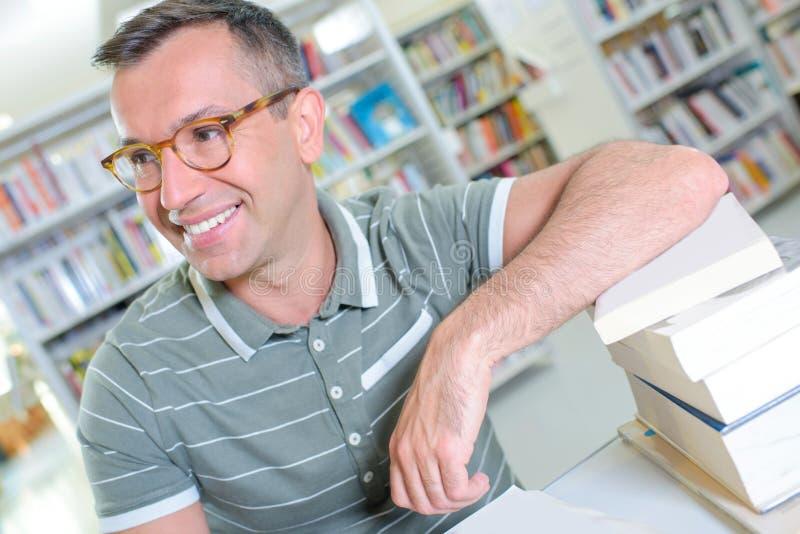 Homme à lunettes se penchant sur des livres de pile images stock