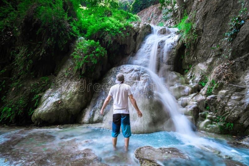 Homme à une cascade dans la jungle images stock