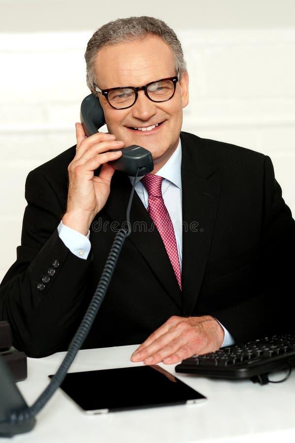 Homme âgé de sourire communiquant avec son client image stock