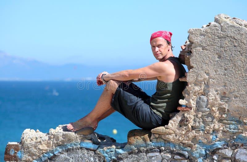 Homme âgé moyen bel s'asseyant sur un mur photos stock