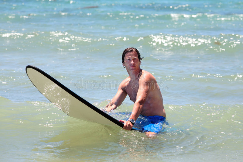 Homme âgé moyen convenable surfant sur la plage en été image libre de droits