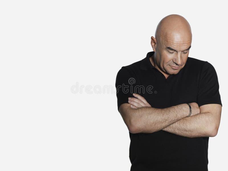 Homme âgé par milieu bouleversé avec des bras croisés photos libres de droits