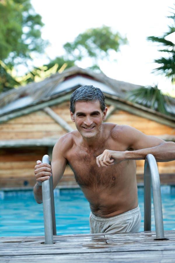 Homme âgé par milieu de sourire se tenant dans la piscine photos stock