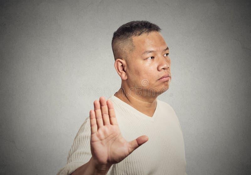 Homme âgé par milieu grincheux avec la mauvaise attitude présentant l'exposé au geste de main photographie stock