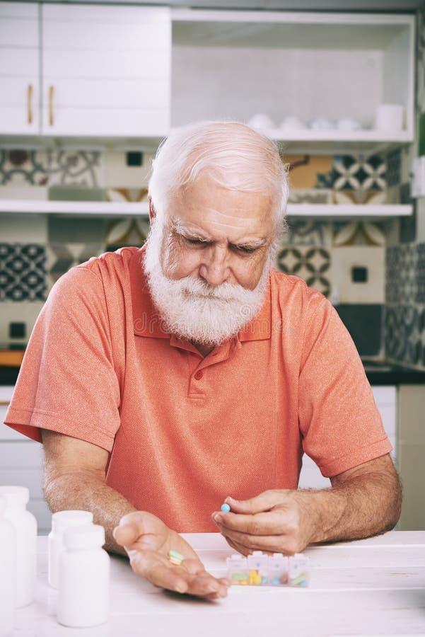 Homme âgé prenant des pilules image libre de droits