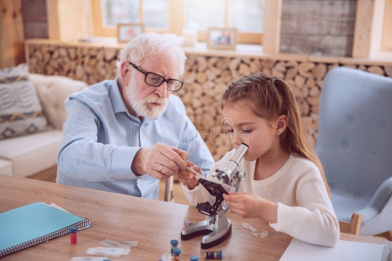 Homme âgé sérieux aidant son élève photographie stock