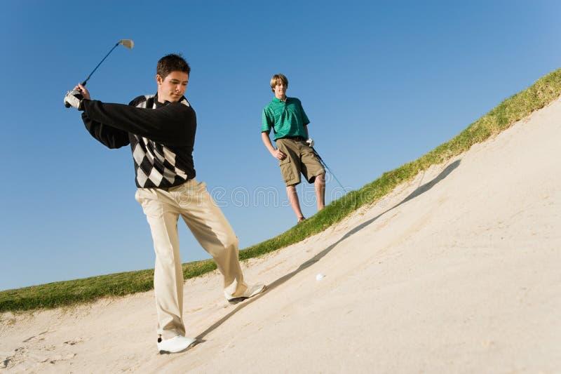 Homme ébréchant la boule de golf hors d'un dessableur photos stock