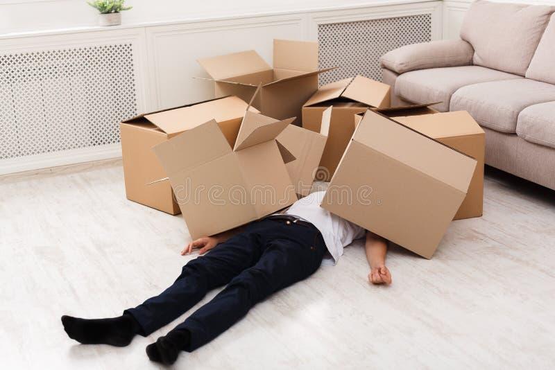 Homme écrasé sous des boîtes en carton photos stock