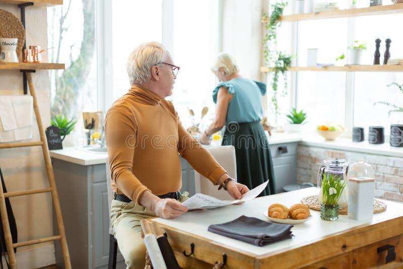 Homme élégant appelle l'épouse tandis qu'elle est occupée avec la cuisson photo libre de droits