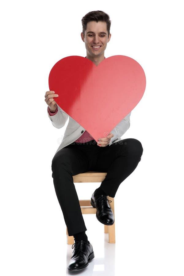 Homme élégant assis tenant le grands coeur et rire images libres de droits
