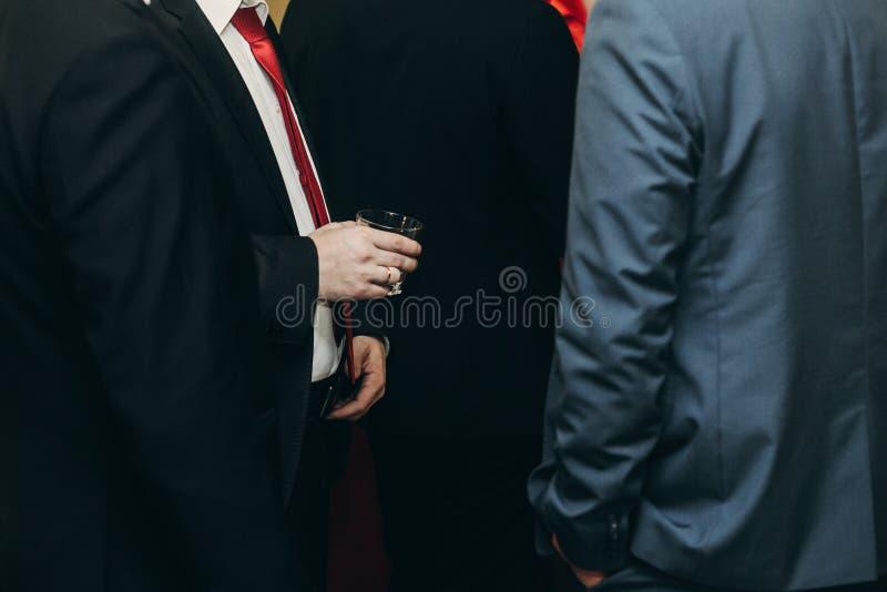 Homme élégant bel avec la boisson d'alcool posant au dinne d'affaires photographie stock