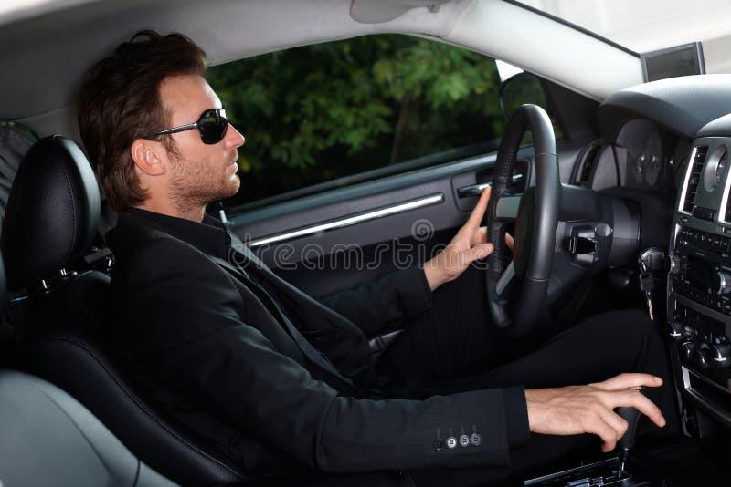 Homme élégant conduisant une voiture photo stock