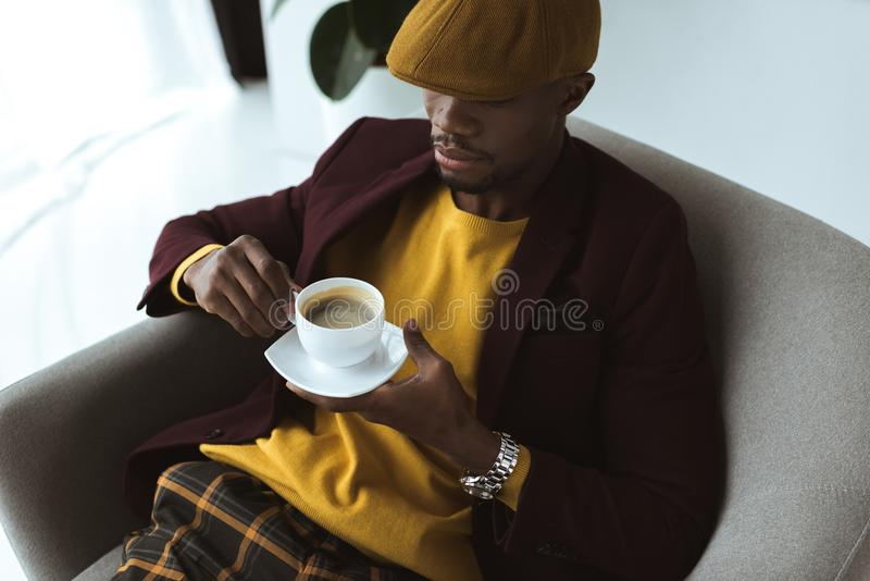 homme élégant d'afro-américain dans le chapeau avec la tasse de café se reposant dans le fauteuil images libres de droits