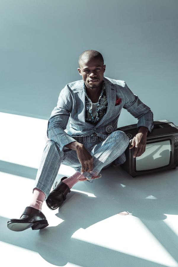 Homme élégant d'afro-américain dans un costume, se reposant sur le plancher avec la rétro télévision et le regard photo libre de droits