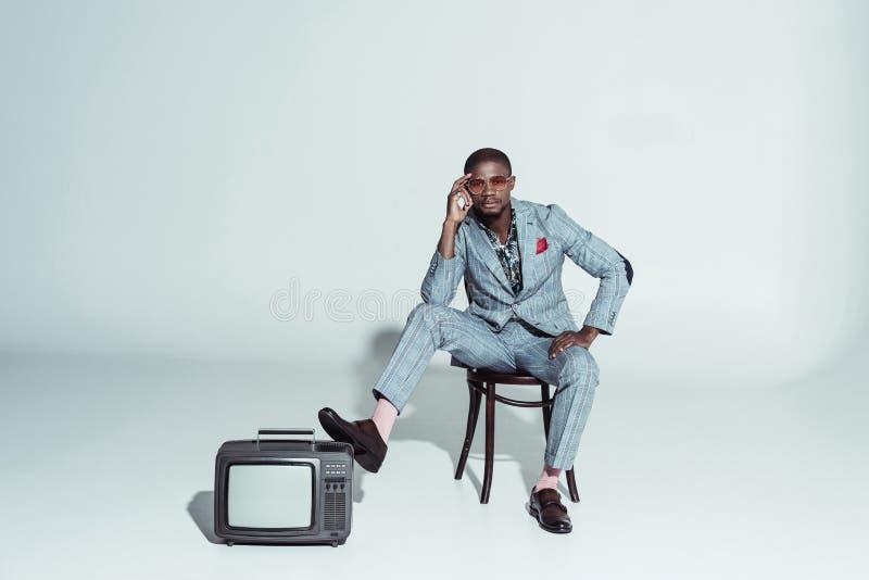 Homme élégant d'afro-américain posant sur la chaise en bois avec une jambe sur a photographie stock libre de droits