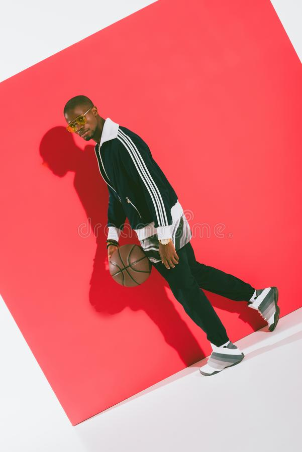 homme élégant d'afro-américain tenant la boule et le regard de basket-ball images stock