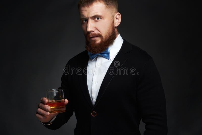 Homme élégant dans le costume et lien buvant d'un whiskey dans le studio photographie stock