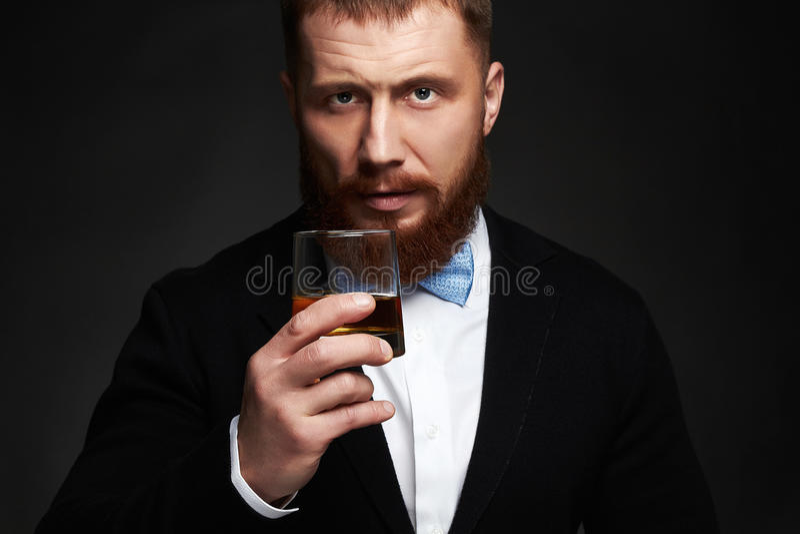 Homme élégant dans le costume et lien buvant d'un whiskey dans le studio photographie stock libre de droits